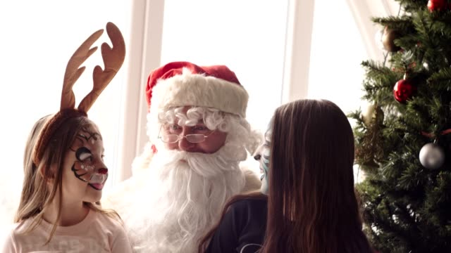 Santa and two young girls with painted face