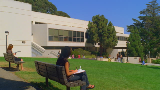 MS Santa Barbara City College humanities building, female student sitting on bench in foreground / California, USA