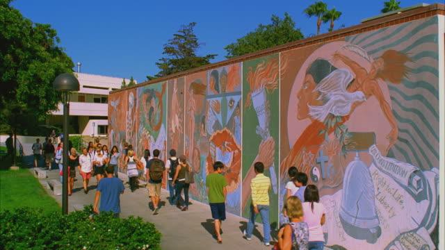 ws santa barbara city college, students passing colorful mural in campus center / california, usa - santa barbara stock-videos und b-roll-filmmaterial