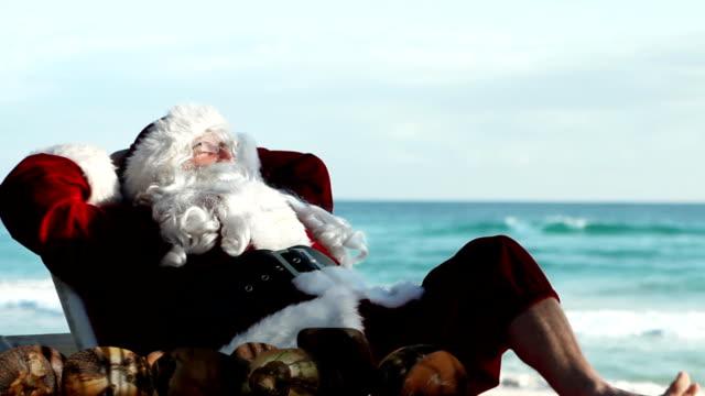 vídeos de stock e filmes b-roll de santa praia relaxante - papai noel