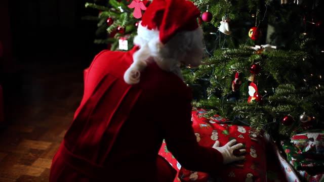 ms tu td r/f santa bringing gift under christmas tree / brussels, brabant, belgium - weihnachtsmütze stock-videos und b-roll-filmmaterial