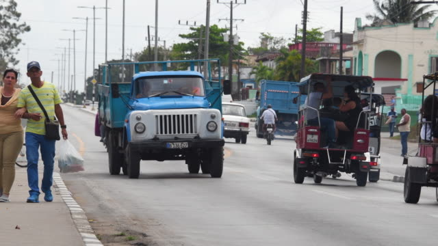 santa clara, cuba: establishing shot with diverse old cars transportation and everyday lifestyle in the capital city of the province of villa clara province - 英字点の映像素材/bロール