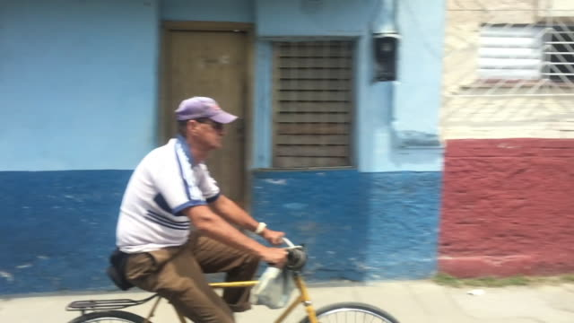 stockvideo's en b-roll-footage met santa clara, cuba: everyday life in slow motion, point of view from a tourist bus during the daytime - communisme