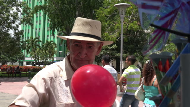 Santa Clara, Cuba: Lifestyles in the Leoncio Vidal park, senior man selling balloons and homemade small toys in the tourist attraction
