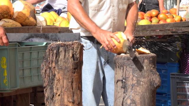 Santa Clara, Cuba: The 'Sandino' Sunday Farmer's Market, opening a coconut with a machete