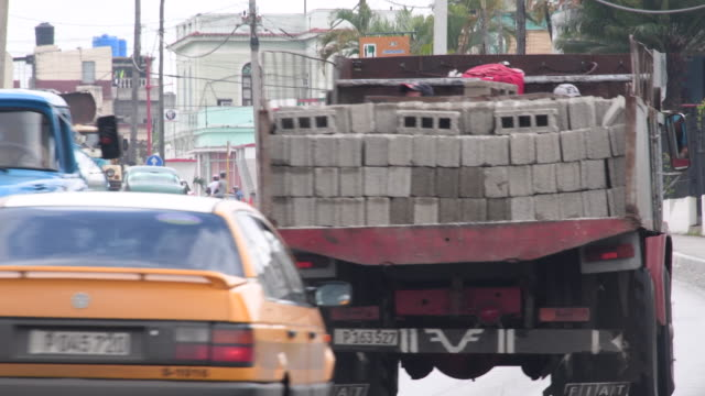 vidéos et rushes de santa clara, cuba: traffic and transportation scene in the central road. the main cuban road traverse the city from one point to the other. - traverse city