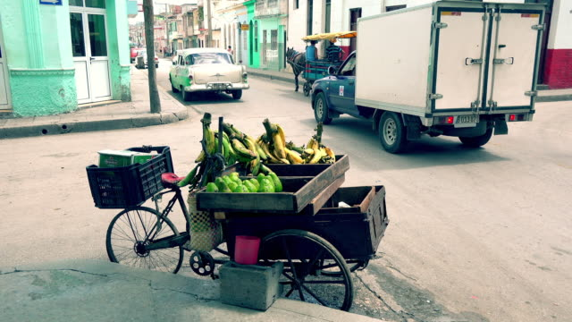 vidéos et rushes de santa clara, cuba, vegetable and fruit stand on a city street - coin