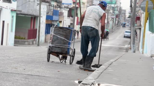 Santa Clara, Cuba: Young man sweeping the streets. His shirt reads 'Lama Sabachthani'