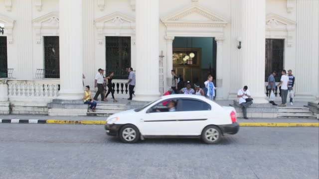 santa clara, villa clara, cuba-september 12, 2019: people wait for transportation or walk in the porch of the landmark building. the library is... - cream coloured stock videos & royalty-free footage