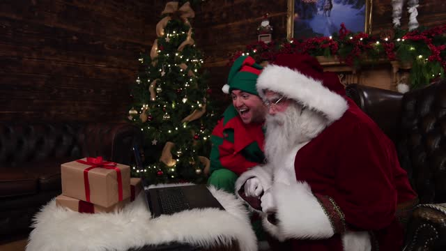 stockvideo's en b-roll-footage met santa claus and his elf pipkin talk to children on zoom on november 27 in newquay, england. a new partnership between santa claus and children's... - zoom out