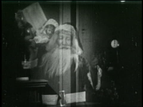b/w 1925 dissolve santa claus appearing with gifts + waving - 1925 stock videos & royalty-free footage