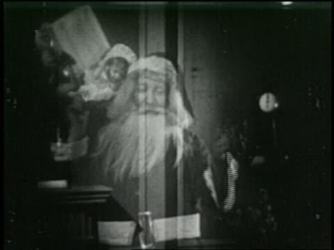 vidéos et rushes de b/w 1925 dissolve santa claus appearing with gifts + waving - 1925