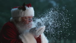 Santa Claus blowing snow from hands in slow motion