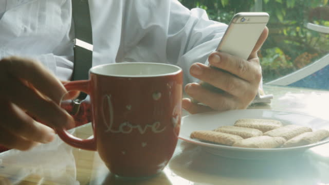 vidéos et rushes de santa claus checking his smartphone while having hot drink. - vêtement de peau