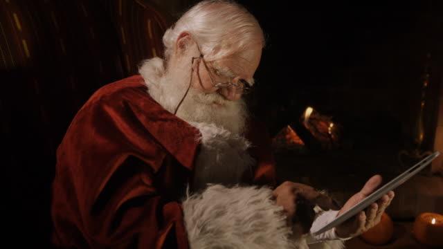 vidéos et rushes de santa claus checking his tablet. - seniornaute