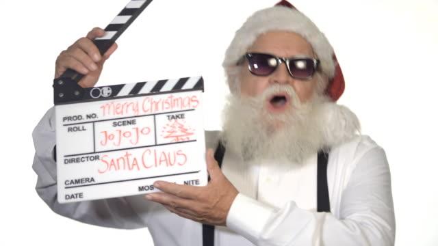 vídeos de stock e filmes b-roll de santa claus clapping a film slate. - papai noel