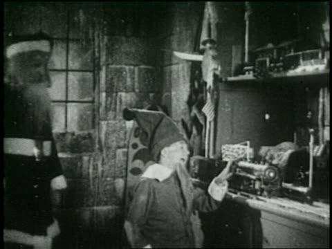 stockvideo's en b-roll-footage met b/w 1925  santa claus + elf look at toy train in santa's workshop - 1925