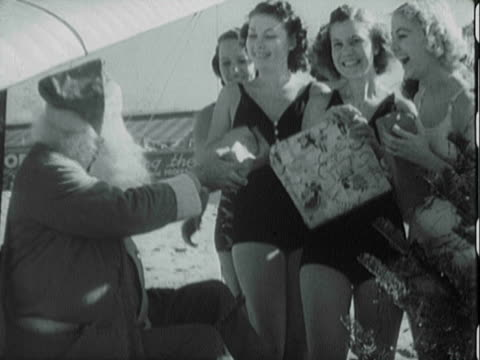 MONTAGE Santa Claus giving out gifts to beach-goers in bathing suits / United States