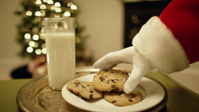 vídeos de stock e filmes b-roll de santa claus' gloved hand picks up a chocolate chip cookie from a tray with a glass of milk on it with a christmas tree and a fireplace in the background on christmas eve - pai natal