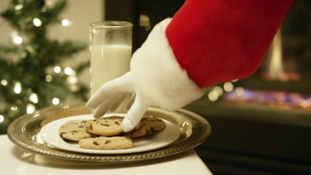 santa claus' gloved hand picks up a chocolate chip cookie from a tray with a glass of milk on it with a christmas tree and a fireplace in the background on christmas eve - chocolate chip cookie stock videos and b-roll footage