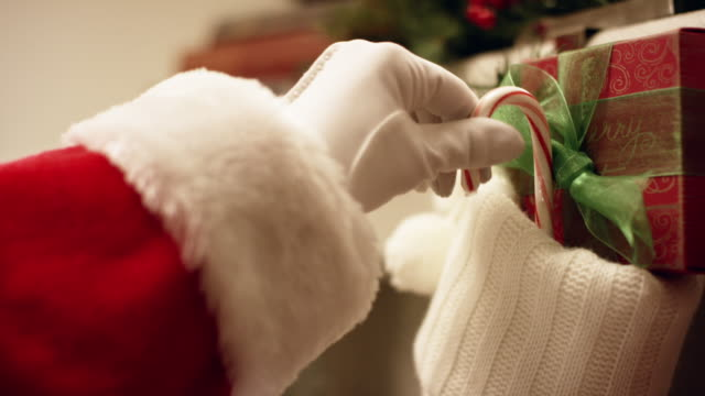 santa claus' gloved hand places a red and white striped candy cane in a christmas stocking hanging from a mantel on christmas eve - stockings stock videos & royalty-free footage