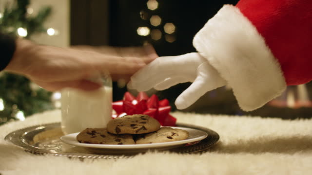 vídeos de stock e filmes b-roll de santa claus' gloved hand tries to pick up a chocolate chip cookie from a tray with a glass of milk on it but a hand swats it away with a christmas tree and a fireplace in the background on christmas eve - pai natal