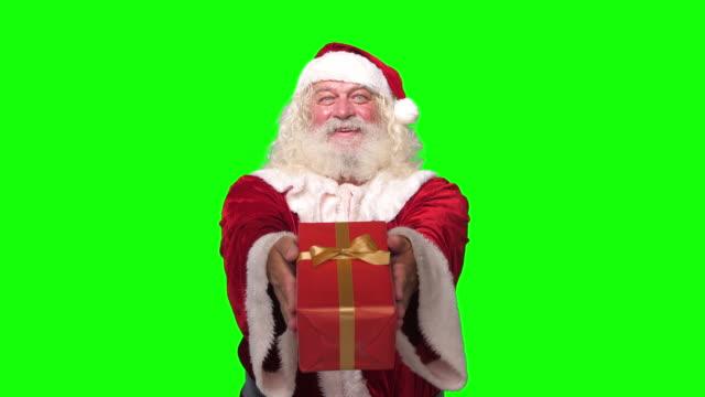 サンタクロースは、クロマキーグリーンの画面の背景の前に笑顔でカメラでクリスマスプレゼントプレゼントを手渡します - クリスマスカード点の映像素材/bロール