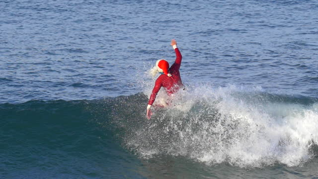santa claus hanging five trick and then wiping out while surfing. - slow motion - california stock videos & royalty-free footage