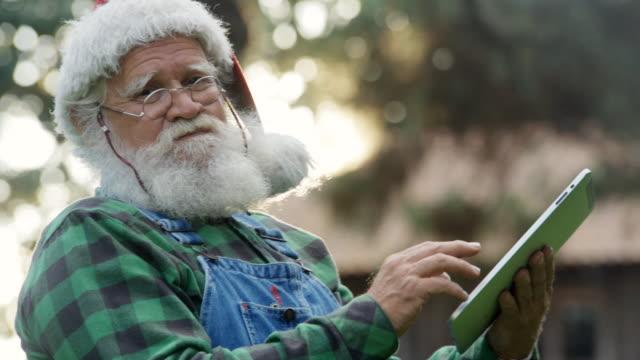 vídeos de stock e filmes b-roll de santa claus having fun with his digital tablet. - idoso na internet