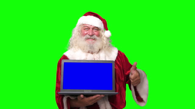 vídeos de stock e filmes b-roll de santa claus holding a laptop with blue screen pointing at it chroma key green screen background - papai noel