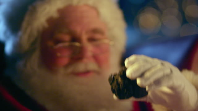 CU Santa Claus holding up a piece of coal and shaking his head