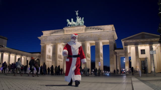 vídeos de stock e filmes b-roll de santa claus in front of brandenburg gate illuminated at night - pai natal