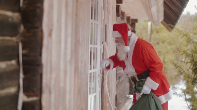 Santa Claus knocking at the door and entering the house (slow motion)