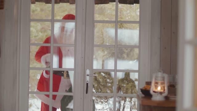 Santa Claus knocking at the door (slow motion)