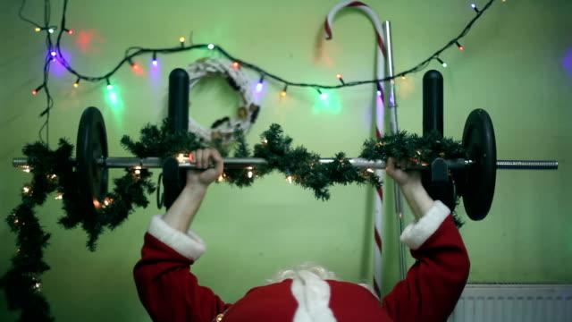 Santa Claus Blick in die Kamera, hebt Gewichte, chrismtas Einrichtung, Beleuchtung, Scherz, lustiger