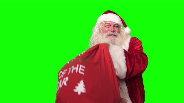 santa claus picking up carrying christmas presents sack bag in front of chroma key green screen background - sack stock videos & royalty-free footage