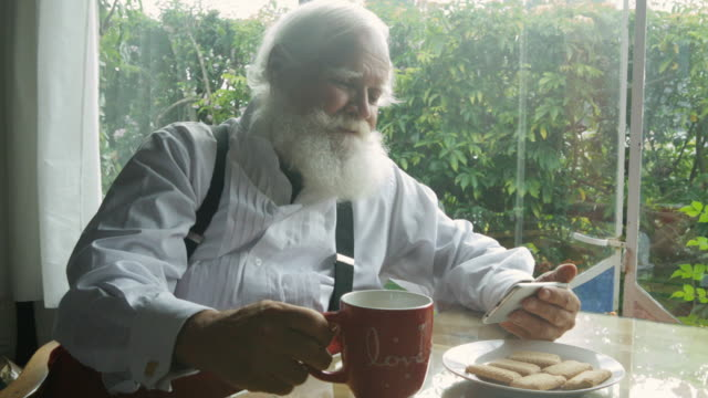 Santa Claus playing with his smartphone during tea time.