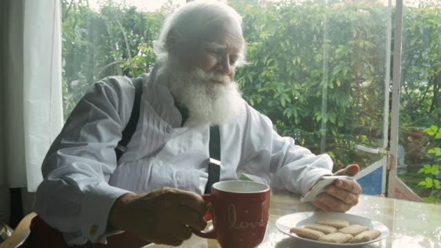 vídeos de stock, filmes e b-roll de santa claus playing with his smartphone during tea time. - cabelo branco