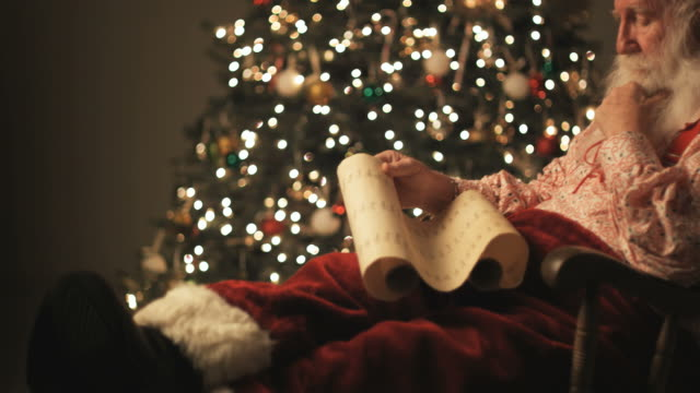 santa claus reading his list of naughty and nice - zusammenstellung stock-videos und b-roll-filmmaterial