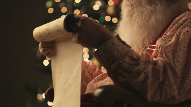 Santa Claus reading his list of naughty and nice