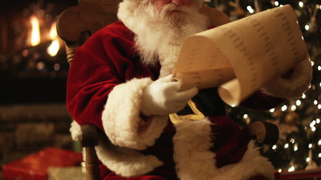 Santa Claus reading his naughty and nice list in a chair by the fire