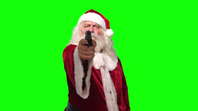 vídeos de stock e filmes b-roll de santa claus robber with a gun threating camera in front of chroma key green screen background - pai natal