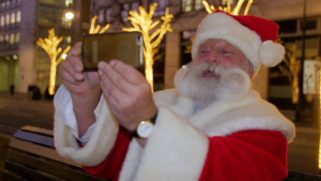 santa claus sitting on bench in city and taking selfie - santa claus stock videos & royalty-free footage
