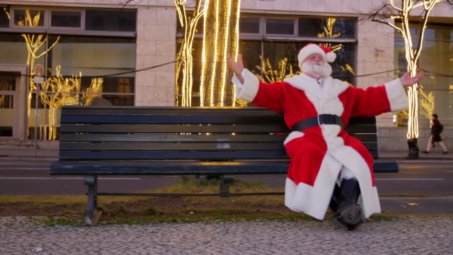santa claus sitting on bench in city and talking to camera - weihnachtsmann stock-videos und b-roll-filmmaterial