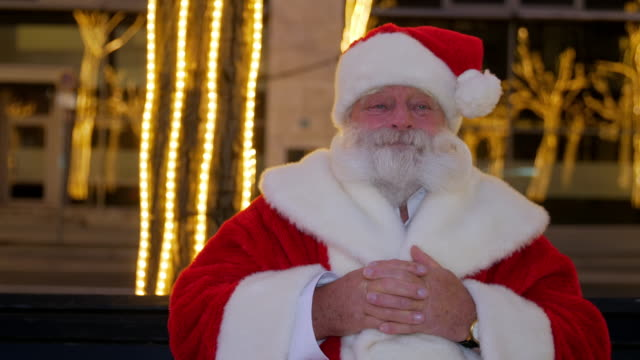 santa claus sitting on bench in city - weihnachtsmann stock-videos und b-roll-filmmaterial