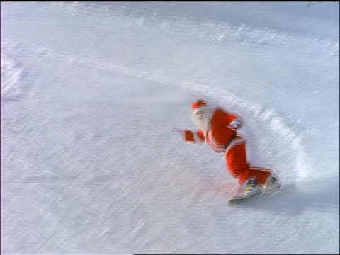 santa claus snowboarding down slope / wipes out at bottom - misserfolg stock-videos und b-roll-filmmaterial