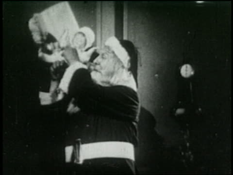 b/w 1925 santa claus taking horn from sack full of gifts - 1925 stock videos & royalty-free footage