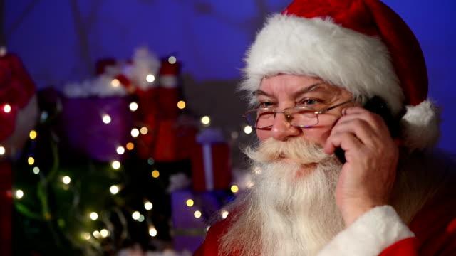 stockvideo's en b-roll-footage met santa claus praten op cell phone - kerstman