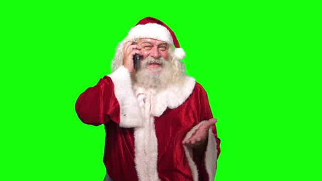 stockvideo's en b-roll-footage met kerstman praten op de telefoon met behulp van smart phone chroma key groen schermachtergrond - 2 5 maanden