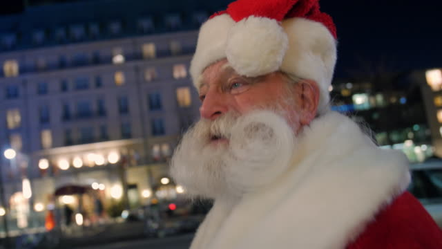 santa claus walking on street illuminated at night - weihnachtsmann stock-videos und b-roll-filmmaterial